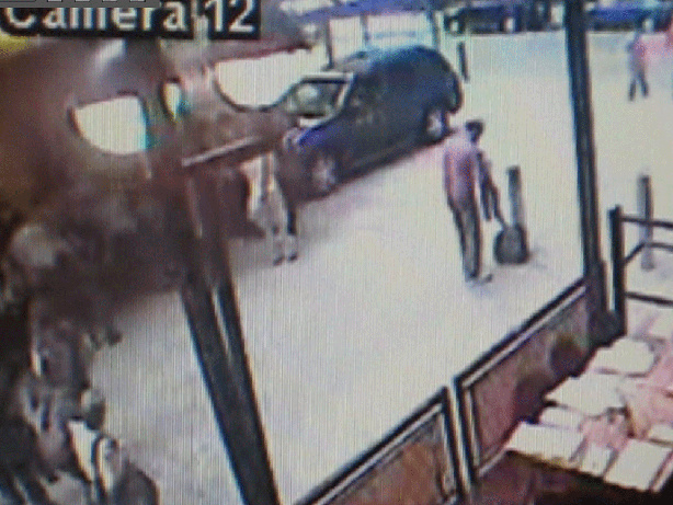 A frame made from a surveillance video released by the New York Police shows a man (right) removing a shirt, not far from where the Pathfinder containing explosive materials was parked.