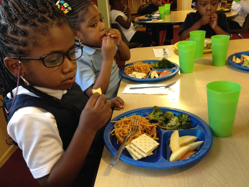 Preschoolers eat lunch of broccoli, turkey pasta, apples and saltine crackers.