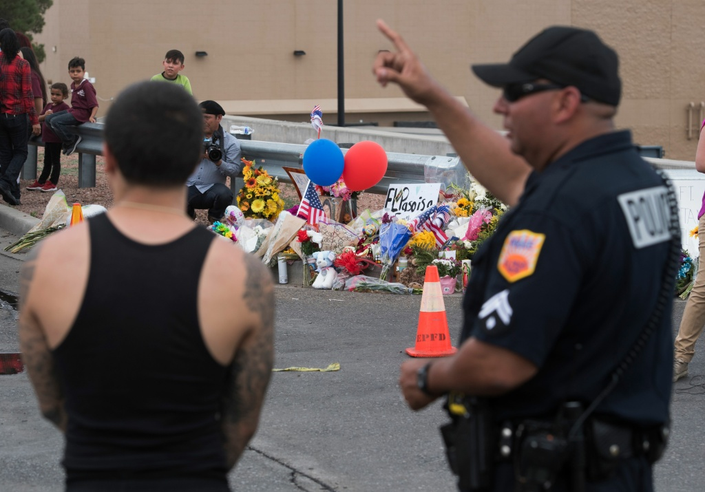 Police and state troopers keep watch outside the Cielo Vista Mall Wal-Mart (background) where a shooting left 20 people dead in El Paso, Texas, on August 4, 2019.