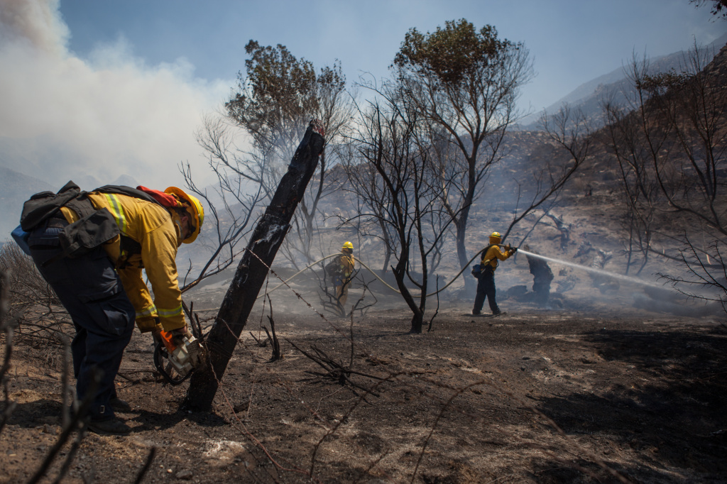 Hayden Harshman of the Oceanside Fire Department chops down a fencepost near homes that are threatened by the Silver Fire.