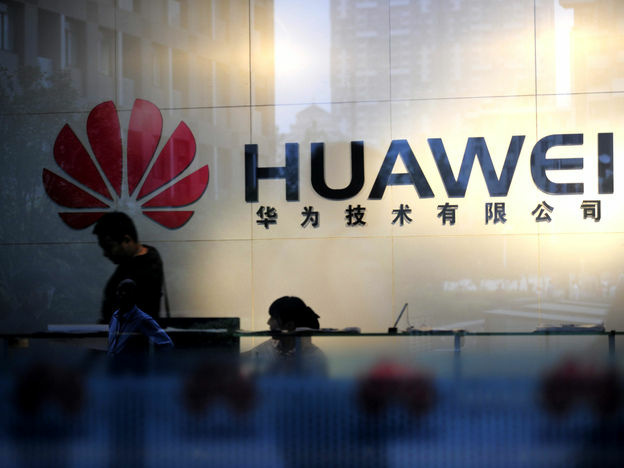 Staff and visitors walk past the lobby at the Huawei office in Wuhan, China. Beijing has urged Washington to