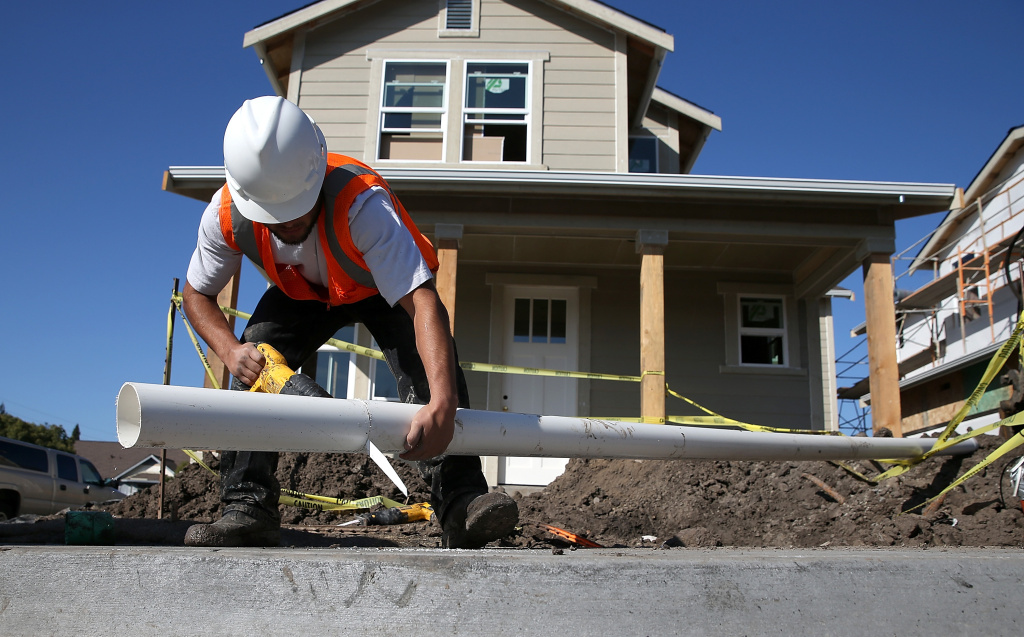 A worker cuts a piece of pipe as he builds a new home on January 21, 2015 in Petaluma, California.