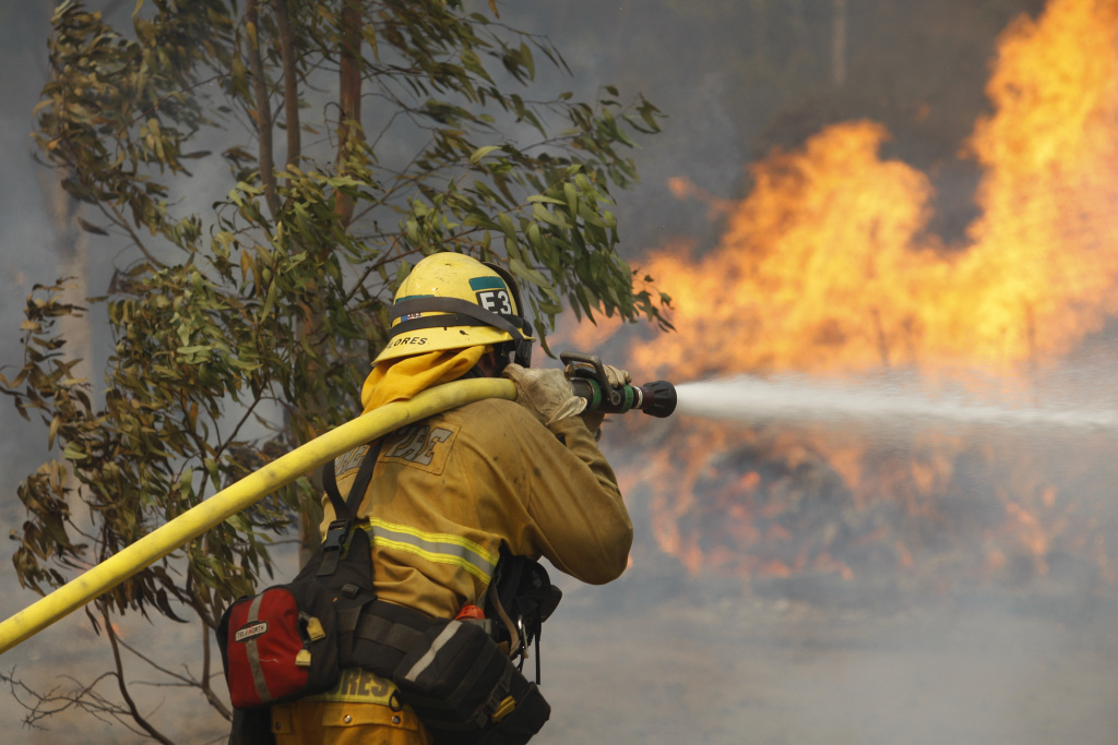 File photo: A firefighter hoses flames at the Cocos fire on May 15, 2014 in San Marcos, California. On Tuesday, Aug. 5, 2014, Agriculture Secretary Tom Vilsack said the money designated for firefighting will soon run out, and in what has become a routine practice, the department will have to dip into funds for programs that help prevent future fires.