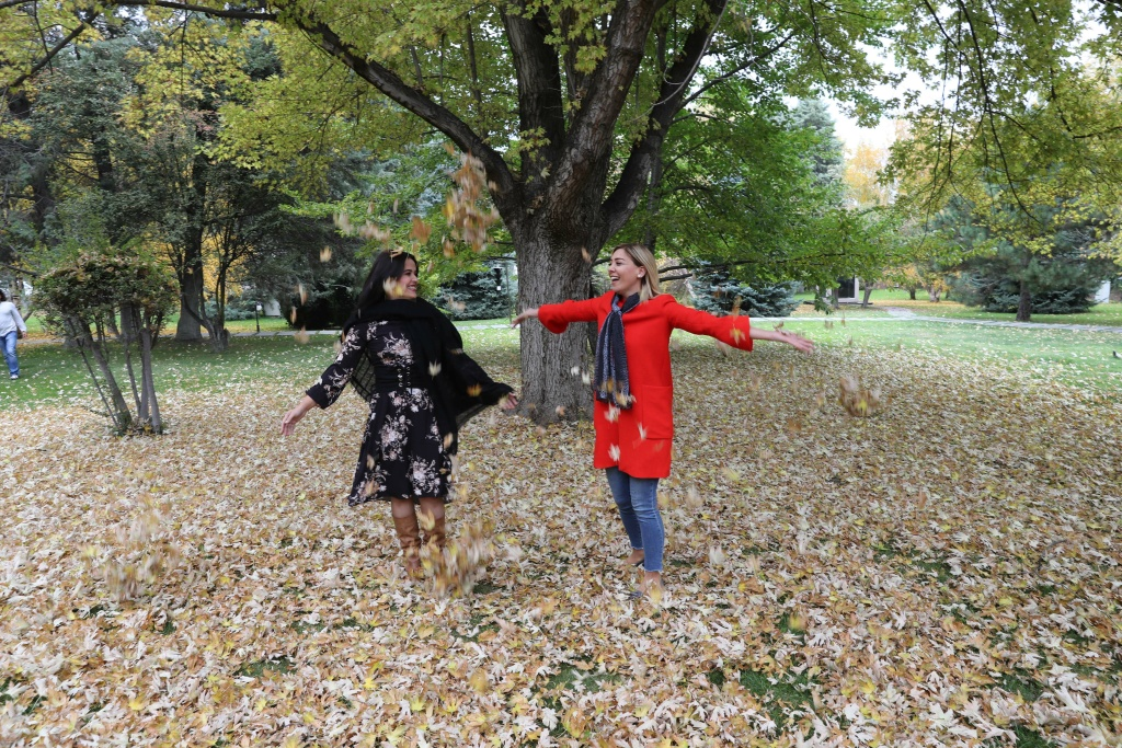 Women enjoy the leaves dropped from a tree displaying autumn colors in Ankara, Turkey on October 25, 2017.