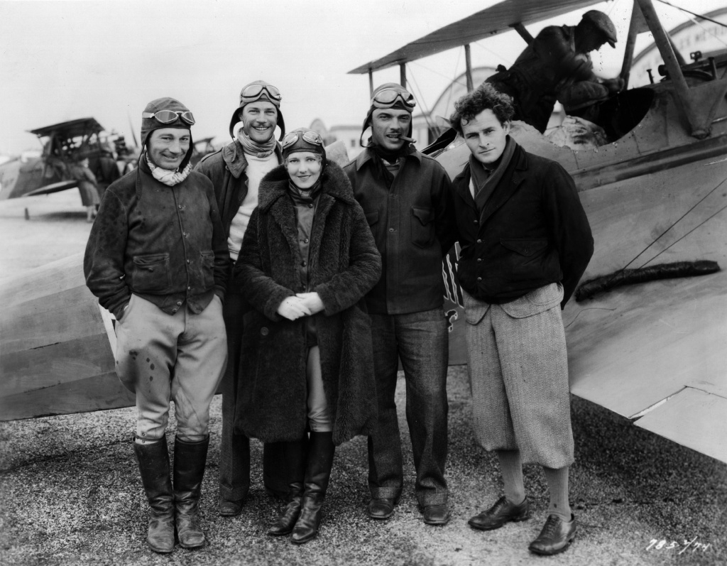 Circa 1930: Leo Nomis, Lt R H Robinson, Jean Arthur and Frank Clark are some of the cast of Paramount's 'Young Eagles', seen with the director William A Wellman (far right) in one of the rare moments when they are all on the ground together.