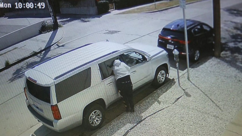 A person burglarizes a vehicle at La Jolla and Melrose avenues in Los Angeles.