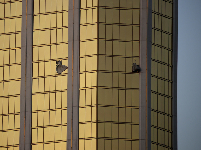 In this Monday, Oct. 2, 2017 file photo, drapes billow out of broken windows at the Mandalay Bay resort and casino on the Las Vegas Strip, following a mass shooting at a music festival in Las Vegas. From two broken-out windows of the resort, Stephen Craig Paddock had an unobstructed view to rain automatic gunfire on the crowd, with few places for them to hide. Sunday night's bloodbath left dozens of people dead and hundreds wounded.
