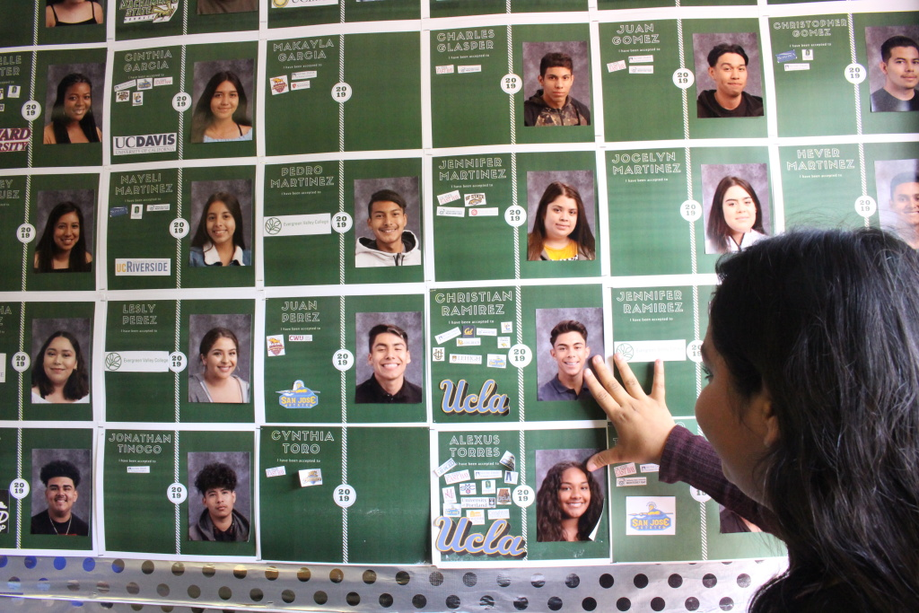 Dafne looks at a wall with images of classmates who have been admitted to college on May 23, 2019.