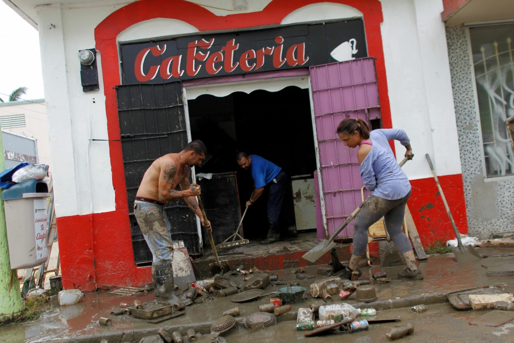 People clean a business damaged when the Arecibo River overflowed in Arecibo, Puerto Rico, September 30, 2017.