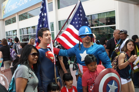Cosplayers dressed as Captain America and Superman, wielding American flags, pose with other fans at San Diego Comic-Con 2014.