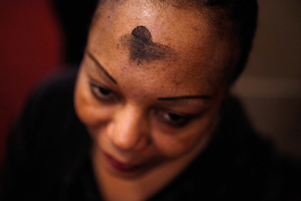 Marked with a cross of black ash on her forehead, a Catholics woman prays during an Ash Wednesday Mass at the Cathedral of St. Matthew the Apostle February 22, 2012 in Washington, DC. Ash Wednesday begins the season of Lent, the 40-day penitential period before Easter when Christians celebrate Christ's resurrection from the dead. One of seven Ash Wednesday services at the cathedral, the noontime mass was packed with worshippers, leaving many to stand in the back and the aisles of St. Matthew.