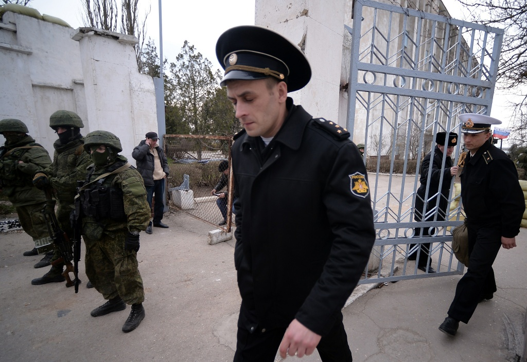 Ukrainian officers leave as Russian soldiers stand guard after they took control of the Ukrainian navy south headquarters base in Novoozerne on March 19, 2014. Russian forces seized control of a second Ukrainian navy base in western Crimea on March 19, hours after capturing the main navy headquarters in Sevastopol. Some 50 Ukrainian servicemen were seen filing out of the base at Novoozerne as Russian soldiers stood by, while pro-Moscow militants raised the Russian flag over the base.