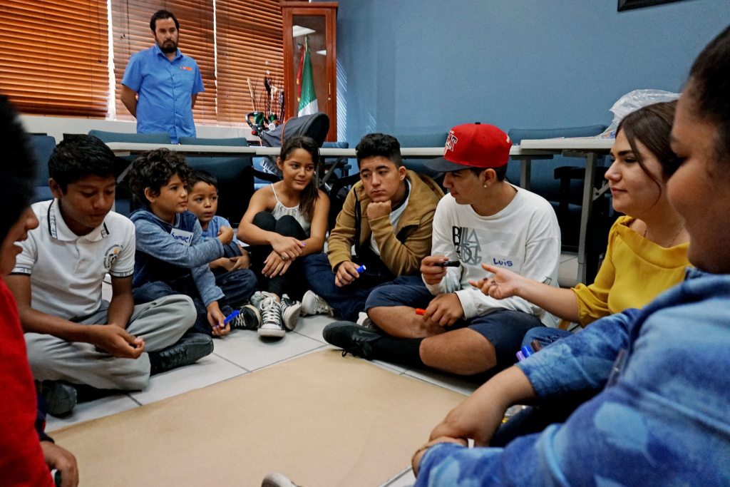 New arrivals to Mexico discuss challenges during a class at the Tijuana Education Department.