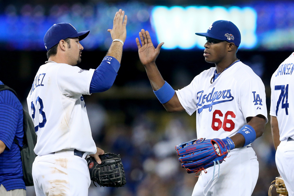 Adrian Gonzalez #23 and Yasiel Puig #66 of the Los Angeles Dodgers celebrate the Dodgers 13-6 victory against the Atlanta Braves during Game Three of the National League Division Series at Dodger Stadium on October 6, 2013 in Los Angeles, California.