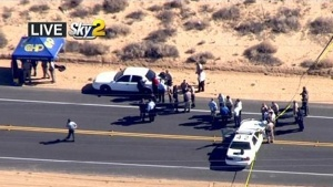 This video image provided by KCBS-TV shows the site of s shooting Friday Oct. 25, 2013 in Ridgecrest, Calif. A homicide suspect was killed by police on this Mojave Desert highway early Friday after a lengthy pursuit in which the man fired at vehicles and two hostages in his car trunk, authorities said.