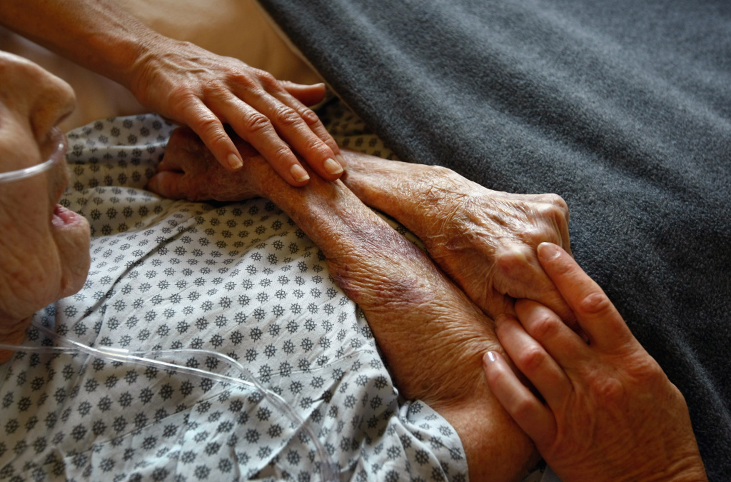 Hospice volunteers caress the hands of terminally ill patient Annabelle Martin, 95.