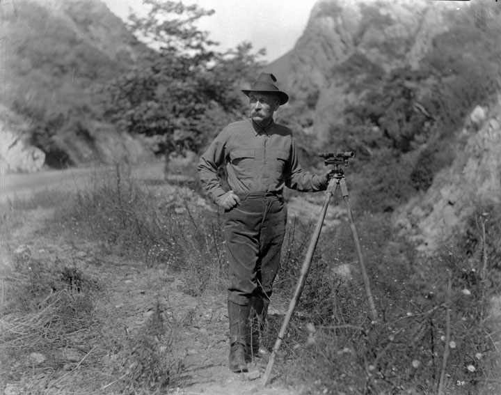 William Mulholland, the chief engineer for building of the Los Angeles Aqueduct, taken in the field, showing him with the surveying instrument whose use he knew so well.