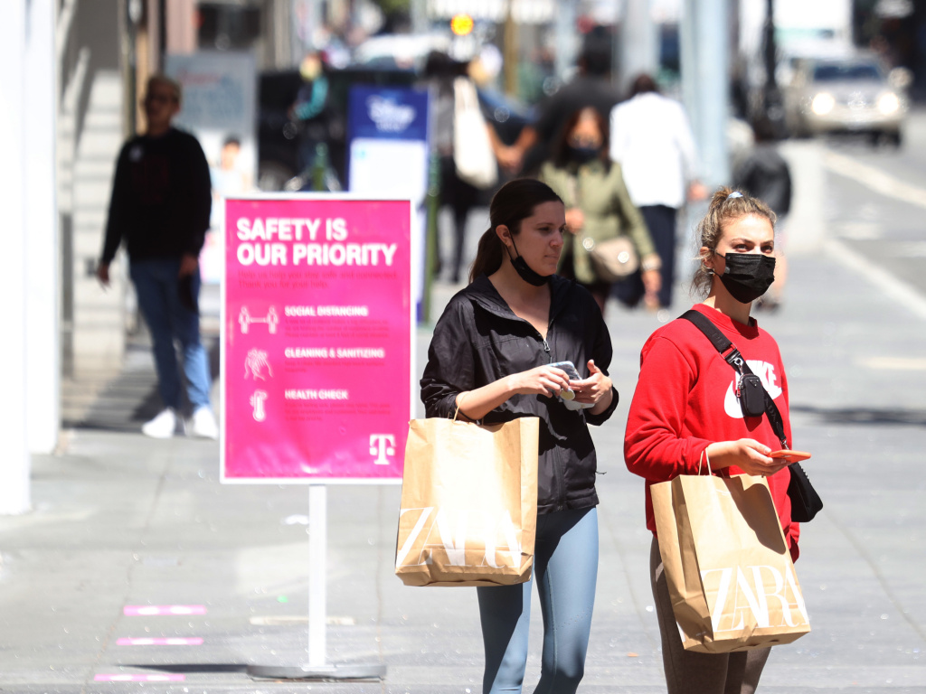 Pedestrians carry shopping bags as they walk through the Union Square shopping district on April 15 in San Francisco. Data on Friday showed personal income jumped 21.1% last month, in what was the largest increase on record.