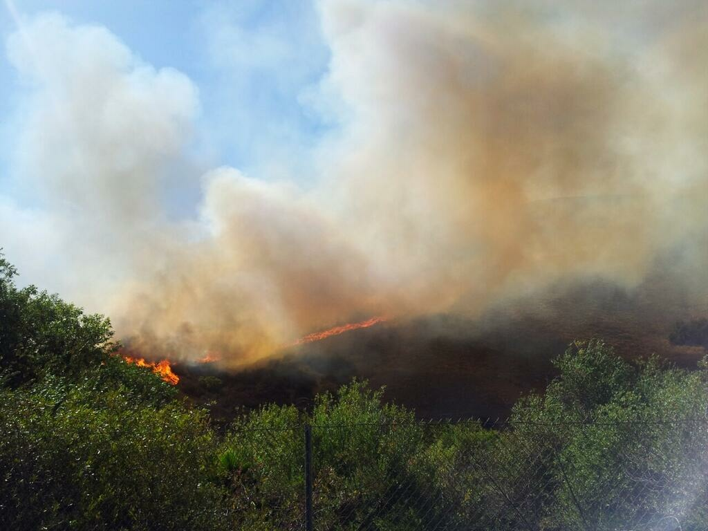 A brush fire close to Calabasas shut down lanes of the 101 Freeway and threatened homes Sunday afternoon, August 18, 2013.