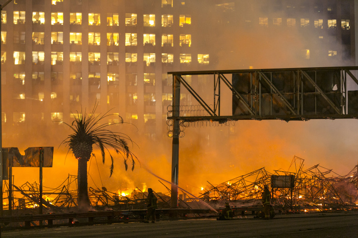 Firefighters continue to spray down a seven-story apartment complex in downtown Los Angeles after an early-morning fire consumed the building on Monday, Dec. 8, 2014.