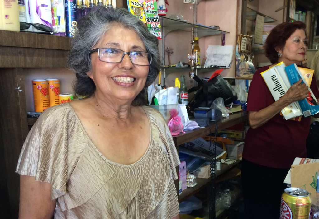 Evelia Diaz, owner of El Batey Market in Echo Park, smiles from behind the counter of her store, which has been open in the neighborhood for 48 years.
