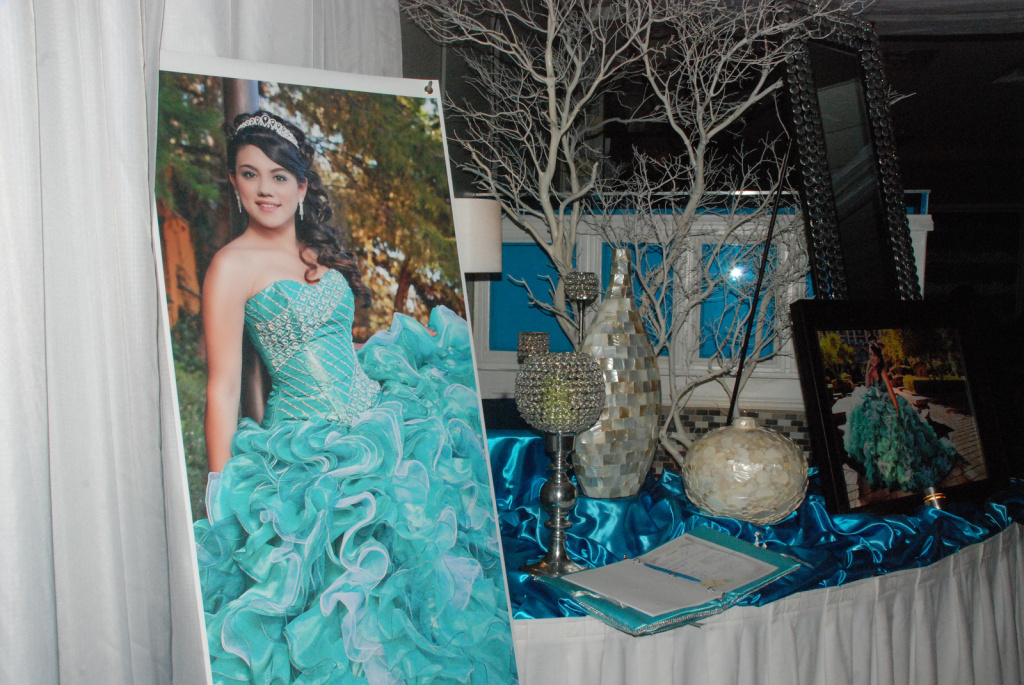 Professional photographs of Julissa Canal greet guests as they enter the hall for her quinceañera.