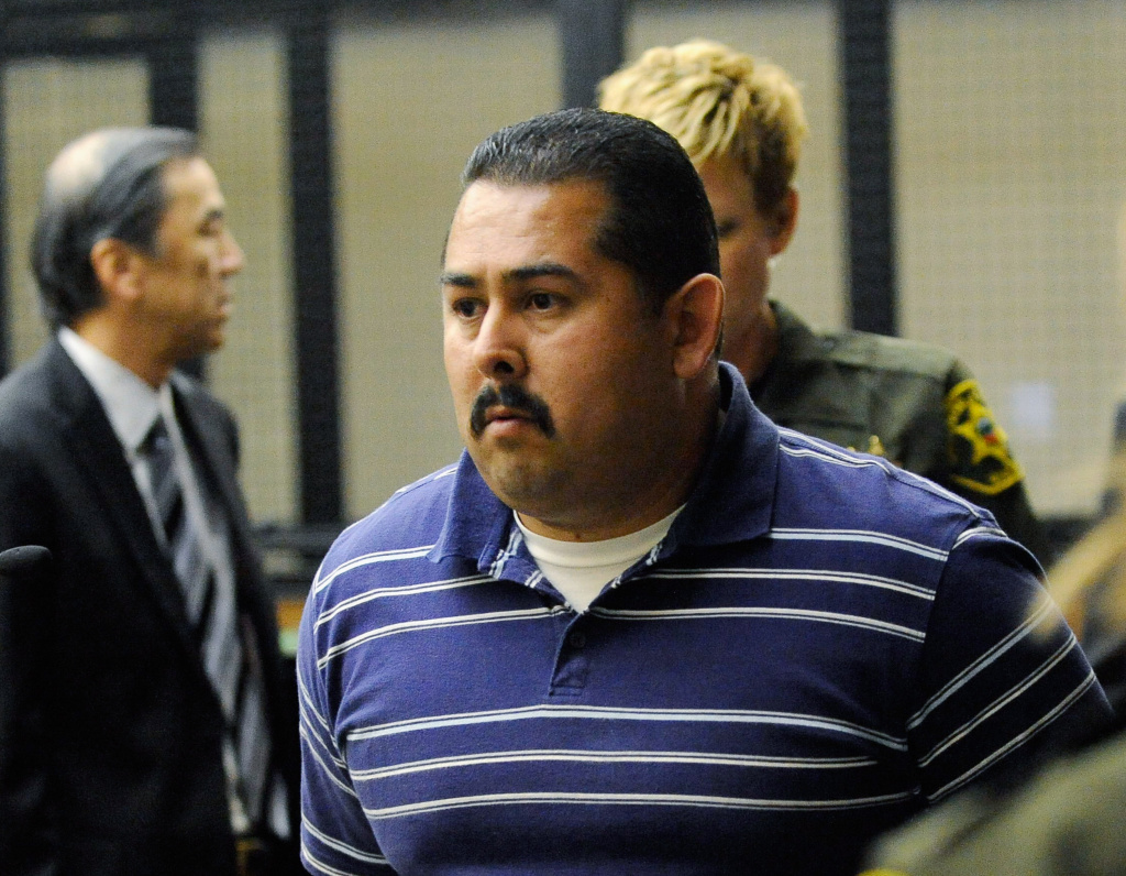 Handcuffed Fullerton police officer Manuel Ramos is charged with second-degree murder and involuntary manslaughter for the death of Kelly Thomas.
