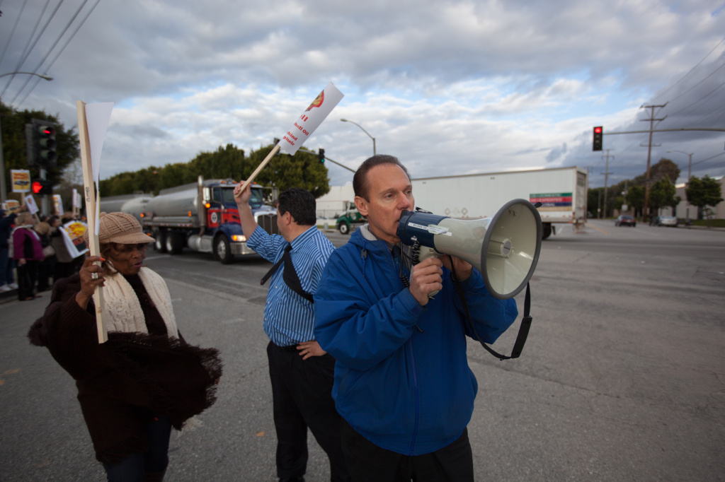 FILE: Jim Dear, then Carson mayor, speaks to protestors outside the Shell Oil facility in South Los Angeles in 2013. Now city clerk, Dear is facing a recall election next week.