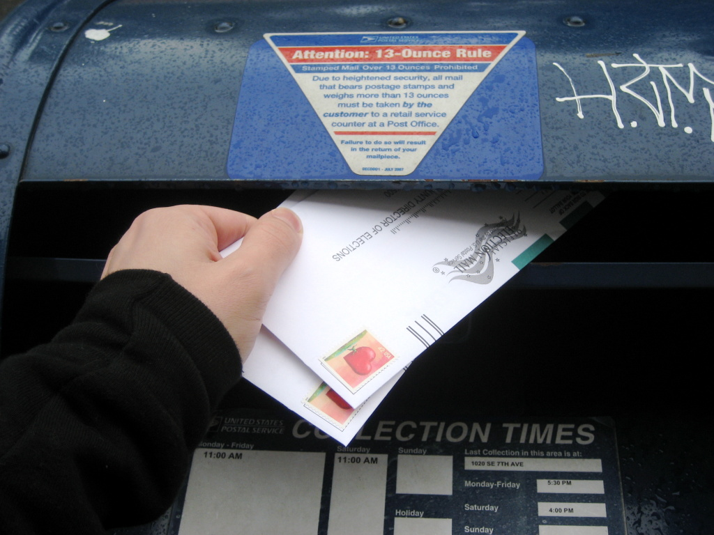 A woman has filled out her ballot and is placing the mail-in ballot into a mailbox.