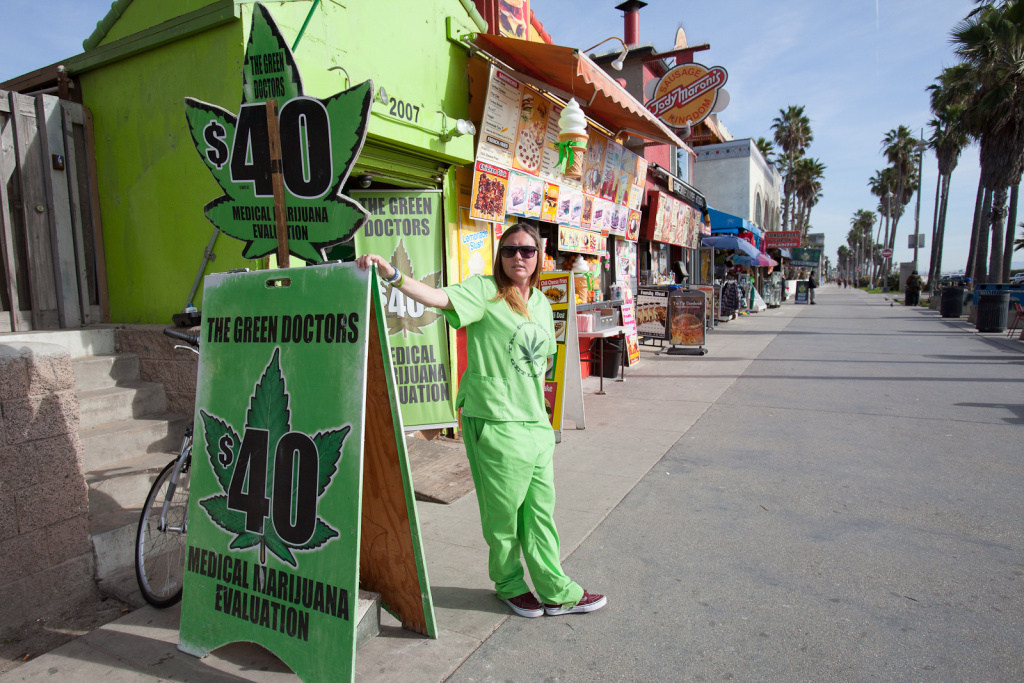 Jenny Mulvaney, Venice, waits for interested patients outside of The Green Doctors, Venice Beach. Despite new rules that say only about 140 medical marijuana dispensaries are eligible to stay open, more than 450 have filed renewals to pay Los Angeles business taxes this year.