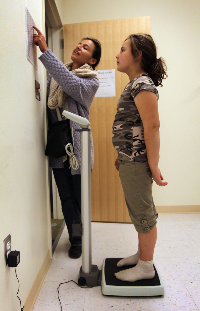 File: Zoe McCoy, 9,  stands atop a scale as her mother Clarisse Gonzalez shows her how much she weighs on November 20, 2010 in Aurora, Colorado.