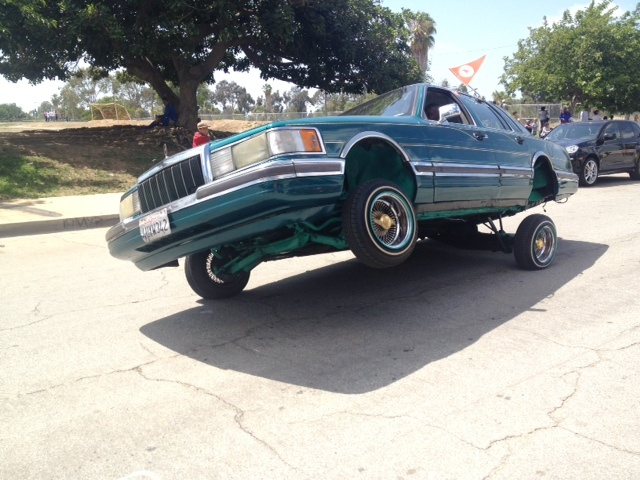 A low-rider car with hydraulics cruises down the street in the