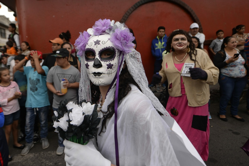 A woman dressed as Catrina takes part in the traditional Convite de fieros festival, as part of All Saints Day celebrations in Villa Nueva, Guatemala, on November 1, 2016.