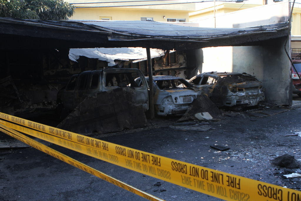 Scorched cars on the 1400 block of Poinsettia Place in Hollywood. Damage from the first wave of arson fires.