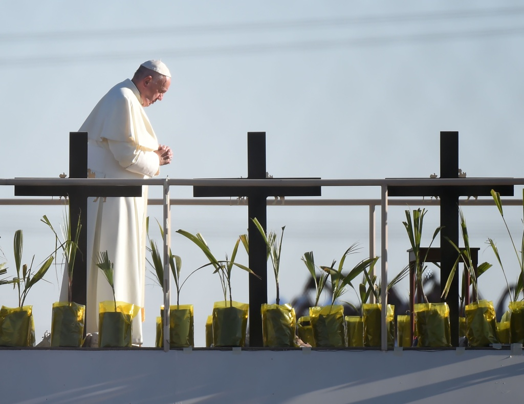 Pope Francis prays besides crosses on a platform in Mexico those who died trying to cross the border at El Paso, Texas on February 17, 2016.