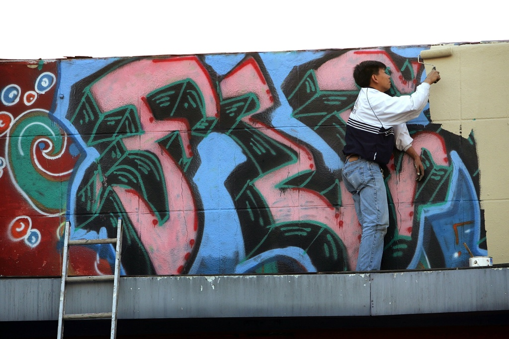 A man paints over graffiti on top of a business on November 1, 2006 in the Koreatown section of Los Angeles, California.