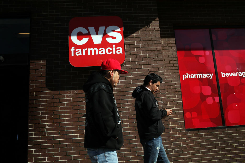 Residents walk by a bilingual sign for a CVS pharmacy on March 28, 2011 in Union City, New Jersey.