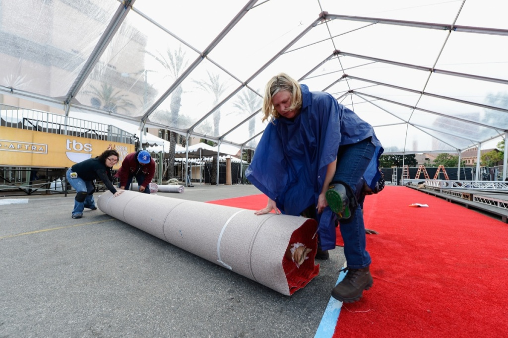 Workers lay down the red carpet during the 19th Annual Screen Actors Guild Awards red carpet roll out and presenter rehearsals at The Shrine Auditorium on Jan. 26, 2013 in Los Angeles.