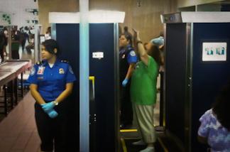 A passenger passes through a full body screener at LAX.