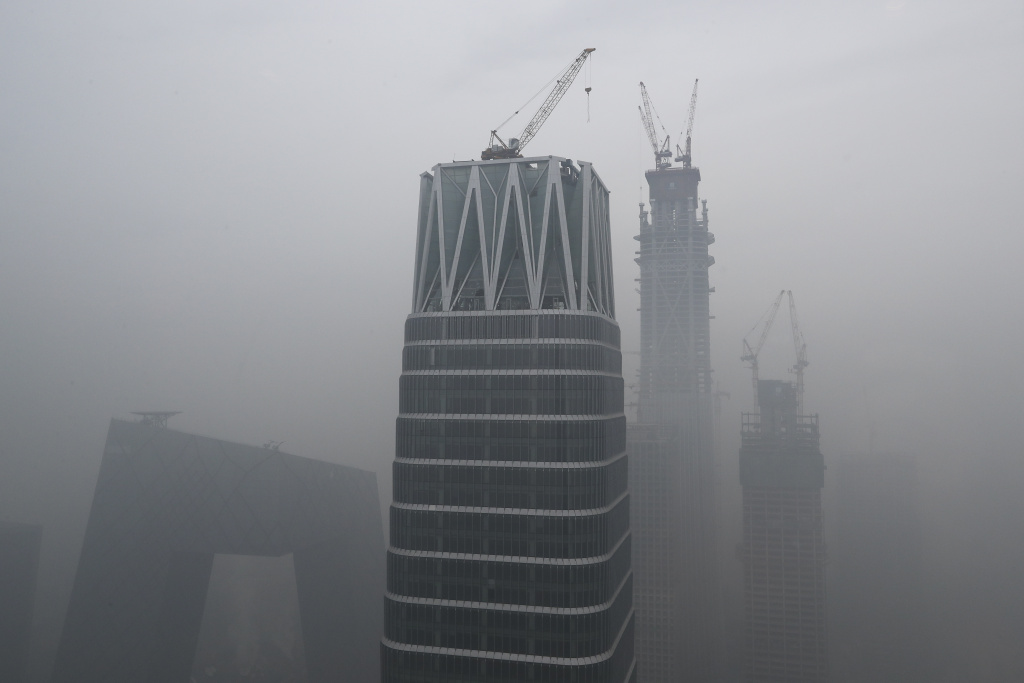 In this Tuesday, Dec. 20, 2016 file photo, China's state broadcaster China Central Television (CCTV) headquarters and construction buildings at the Central Business District are shrouded by heavy smog in Beijing. Thick, gray smog fell over Beijing on Tuesday, choking China's capital in a haze that spurred authorities to cancel flights and close some highways in emergency measures to cut down on air pollution. (AP Photo/Andy Wong, File)