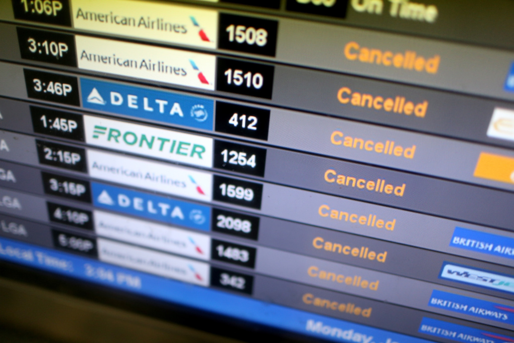 File:  A departure board lists cancelled flights at Miami International Airport on January 26, 2015 in Miami, Florida.