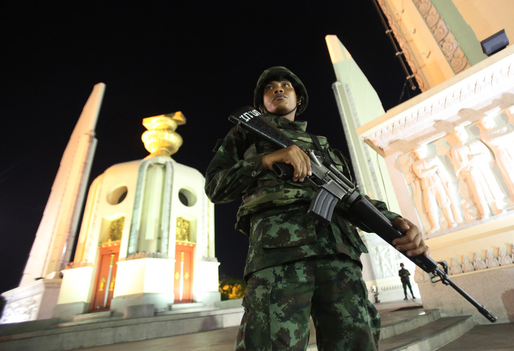 A Thai soldier stands guard in front of the Democracy Monument after the coup Thursday, May 22, 2014 in Bangkok, Thailand. Thailand's military seized power Thursday in a bloodless coup, dissolving the government, suspending the constitution and dispersing groups of protesters from both sides of the country's political divide who had gathered in Bangkok and raised fears of a violent showdown.