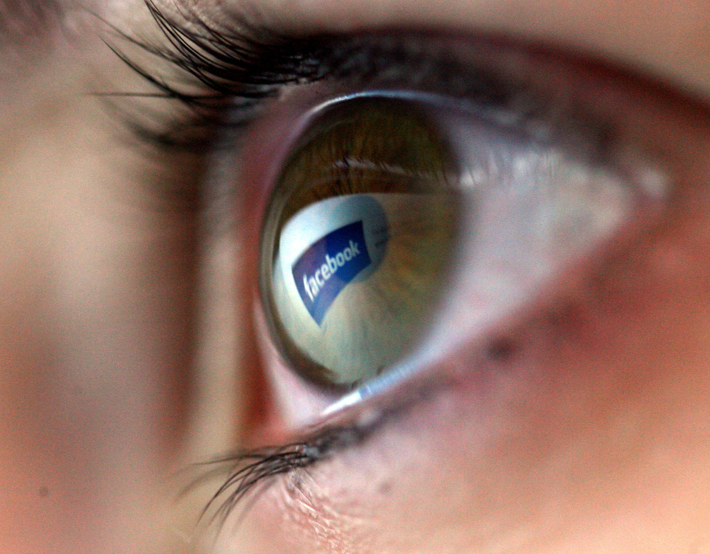 The Facebook logo is reflected in the eye of a girl surfing the internet.