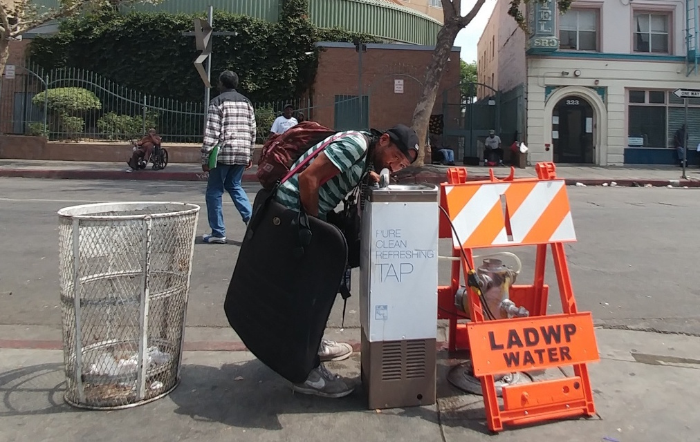 A resident of Skid Row takes a drink from one of the neighborhood's new drinking fountains. The fountains were installed to keep the area's homeless population hydrated during high temperatures.