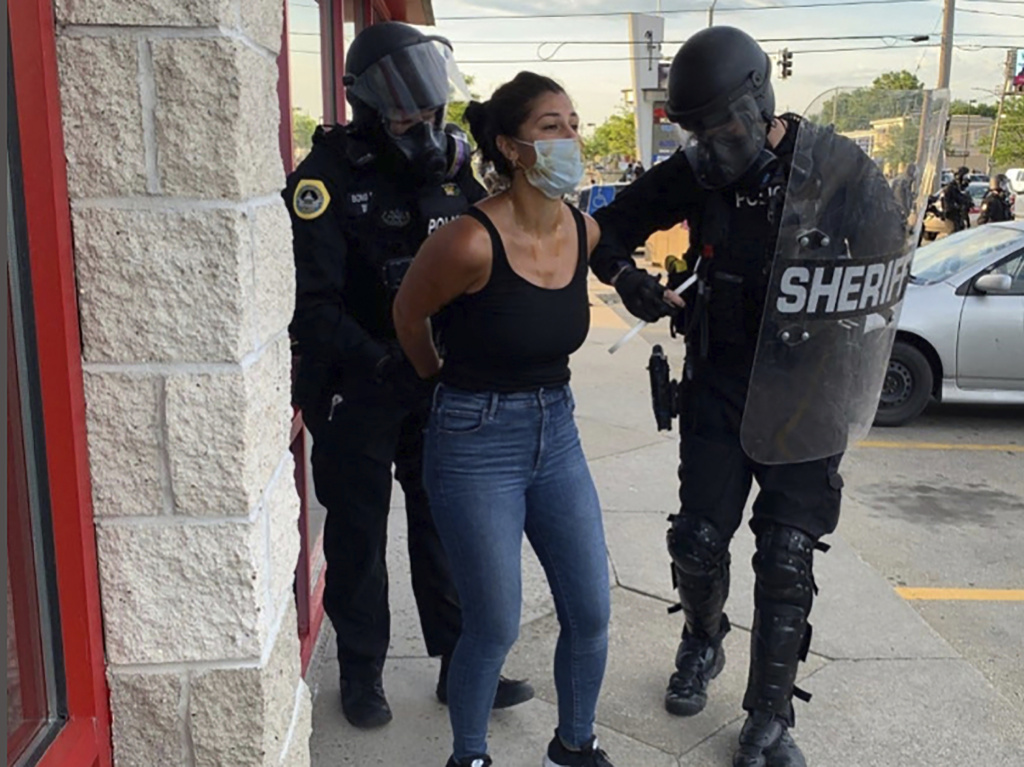 Police officers are shown arresting <em>Des Moines Register</em> reporter Andrea Sahouri after a Black Lives Matter protest she was covering on May 31, 2020, in Des Moines, Iowa. Sahouri went on trial Monday on charges of failing to disperse and interfering with official acts.