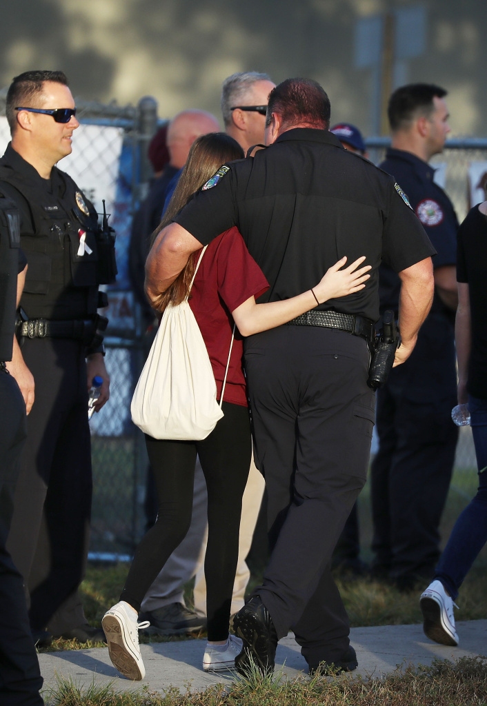 A police officer hugs a student as she arrives for classes at Marjory Stoneman Douglas High School for the first time since the shooting that killed 17 people on February 14 at the school on February 28, 2018 in Parkland, Florida.