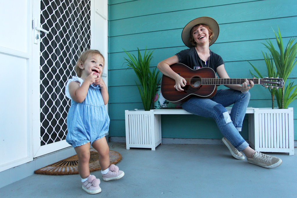 Ashleigh Dallas a Golden Guitar Winning musician plays guitar on her front porch whilst isolating at home with young daughter Harriet on April 06, 2020 in Tamworth, Australia.