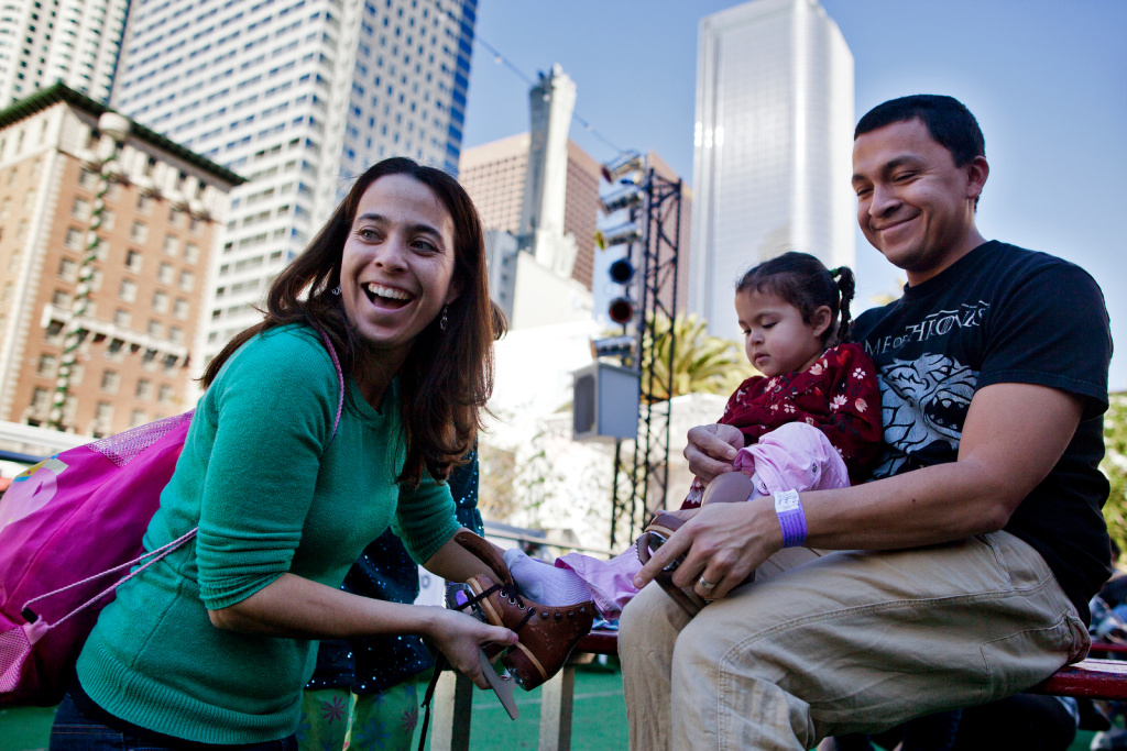 File: Monica, left, and Juan put shoes on her two-year-old daughter, Juliana, before her first time skating during Downtown on Ice at Pershing Square on Christmas Eve in 2013.