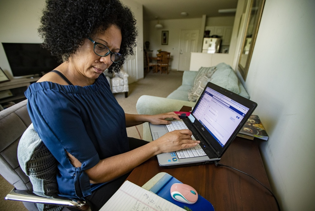Care resource coordinator Luisa Schaeffer scrolls through her COVID-19 isolation case list for the day: One woman is out of milk, while another needs help finding a doctor and making an appointment. A man also asks about getting help to pay rent.