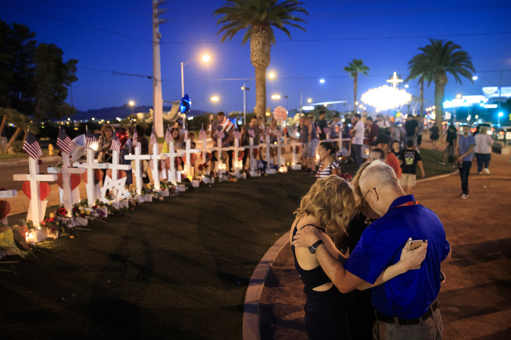 A small group prays at a makeshift memorial with 58 white crosses, one for each victim, on the south end of the Las Vegas Strip, October 6, 2017 in Las Vegas, Nevada.
